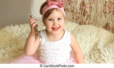 Baby girl talking on the phone, smiles and laughing.