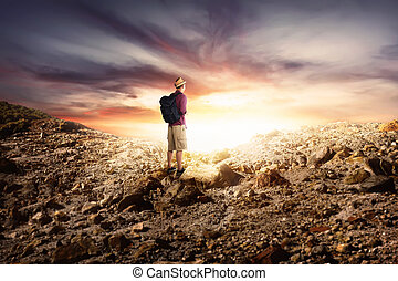 Young asian man with backpack hiking in rocky mountains