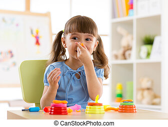 Kid girl playing with plasticine at home or kindergarten -...