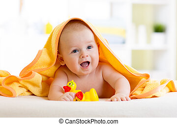 Cute baby with toys under a hooded towel after bath - Cute...