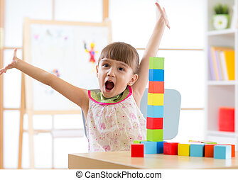 kid playing with block toys in day care center - happy kid...