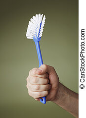 Dish brush - A Hand holding a dish brush