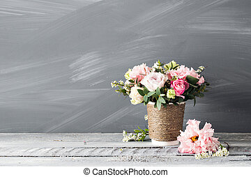 rustic cup with flowers and chalkboard on gray background....