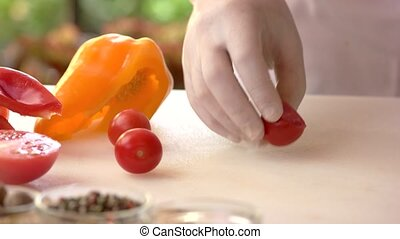 Hand cutting cherry tomatoes. Vegetable on a cooking board.