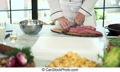 Male hands cutting raw meat. Pieces of veal.