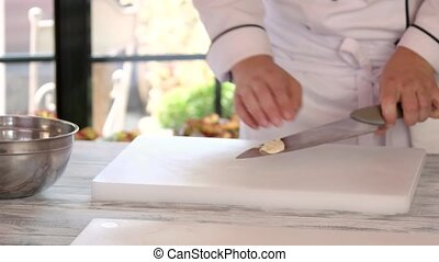 Chef's hands and cutting board. Raw meat and garlic. Make...