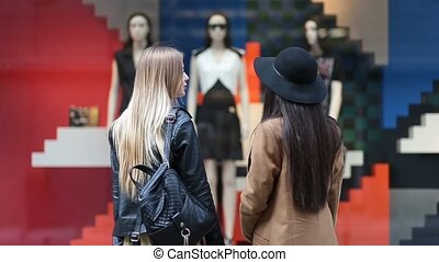 Rear view of cute girls looking at store display - Rear view...
