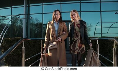 Happy women coming out of shopping mall with bags