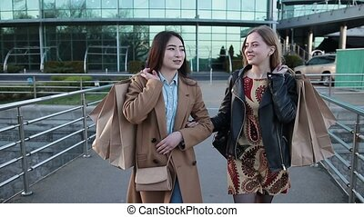 Young cute multiethnic girls with shopping bags - Young...