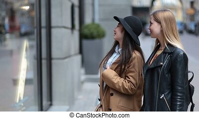 Two young women looking at clothing store window - Two...