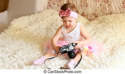 Baby holding a retro camera in hands