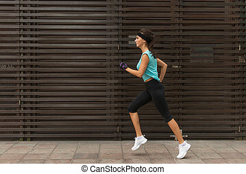 Side view of sporty young woman running on a sidewalk. -...