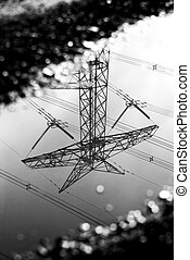 Reflection of transmission tower in a puddle - Reflection in...