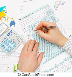 Business man filling out 1040 US Tax Form with calculator...