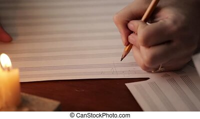 student writing a music: musician composing with a pencil in a music book with candlelight. close-up hand of musician