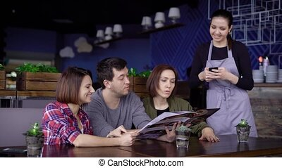 The company of adult friends makes an order for the menu in...