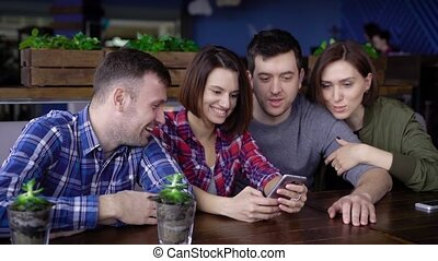 Two couples of friends who are happy with a pleasant time together make photos for memory on a mobile phone in a restaurant where they recently ordered dinner for a company
