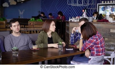 Four friends sit at a wooden table in a cafe and drink coffee, they discuss business plans in a relaxed atmosphere, with a cup of cappuccino