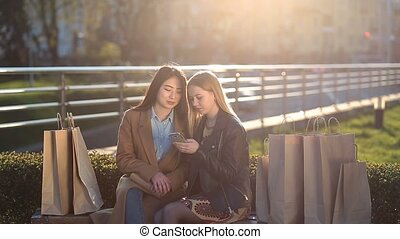 Two girls texting with friends in social network - Two...
