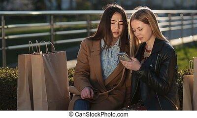 Smiling women browsing internet on mobile phone - Smiling...