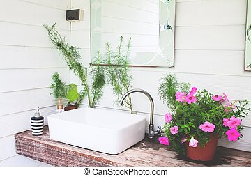 Washbasin with pink flowers in home garden, White and...
