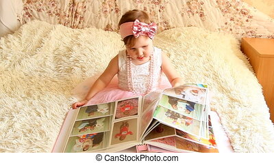 The child holds a photo album in his hands and looks at the...