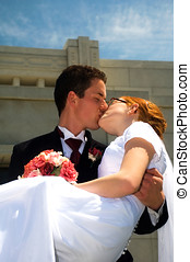 Groom carrying bride and kissing her