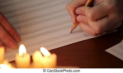 student writing a music: musician composing with a pencil in...