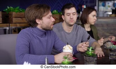 An adult middle-aged man with blond hair and a beard, dressed in a purple sweater, drinks with pleasure frappuchino coffee with whipped cream