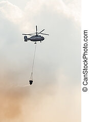 Fire fighter helicopter with loaded water basket on it's way...