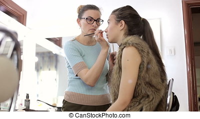 Make-up artist applying cosmetics to model. Beauty and...
