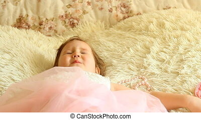 The child lies down to sleep on the bed and closes his eyes.