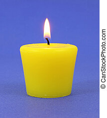Yellow citronella candle that is lit on a blue background.
