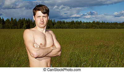 Naked young man on background of field