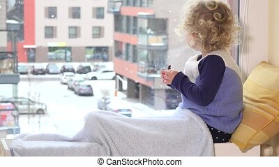Adorable kid eat food and enjoy winter snowstorm outside...