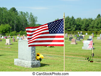 Small American flag waving in cemetery - A small American...
