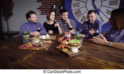 On the wooden table in the restaurant there are a lot of vegetarian snacks, in the background a company of friends is sitting who drinks red wine and has a good time together