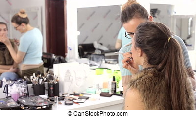 Model getting make up applied by before photoshooting