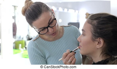 Model getting make up applied by before shooting