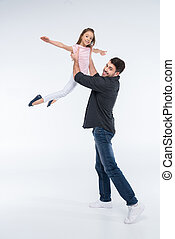 cheerful father playing with daughter on white