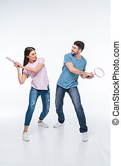 couple playing with badminton rackets on white
