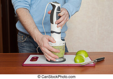man prepares in a blender dessert, smoothies, apples