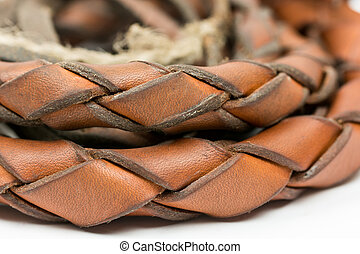 Leather whip isolated over white background closeup macro.
