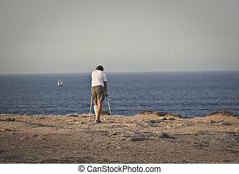 Man on beach - Handicapped man walking on beach