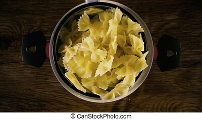 The pasta is shaking in a colander. Slow motion, top view -...