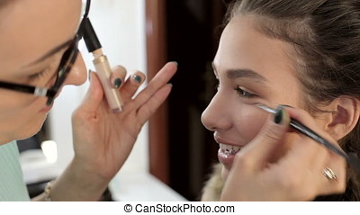 Applying cosmetics to beautiful model. Beauty and fashion