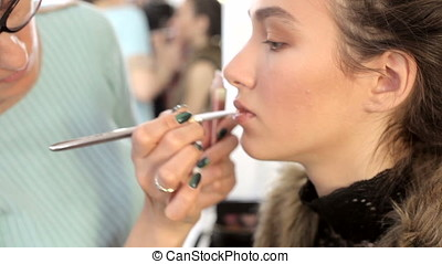 Make-up artist applying lipstick to model