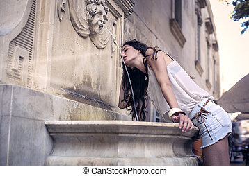 Woman at fountain - Woman drinking from fountain