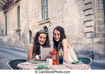 Women in restaurant - 2 women looking at tablet in...