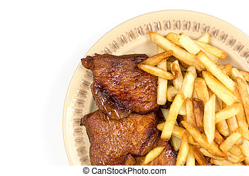 Baked pork chops with french fries served on the plate